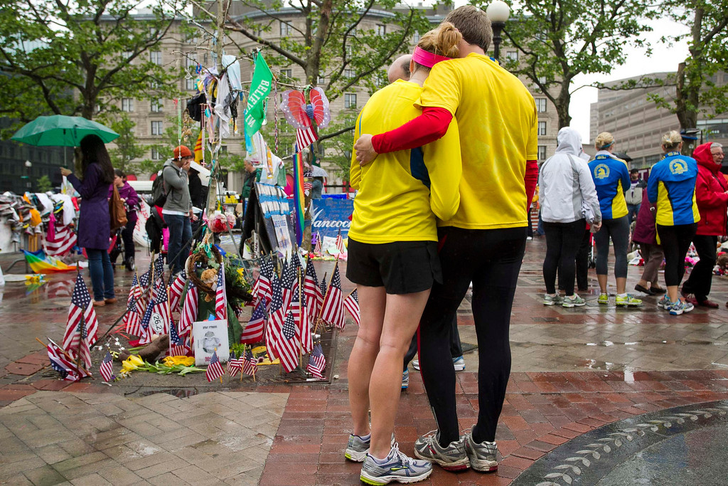 """. Katie Eastman (L) and Kiaren Shaughnessy visit the memorial on Copley Square after crossing the finish line and completing the final mile of the Boston Marathon course during \""""#onerun\"""" in Boston, Massachusetts, May 25, 2013. Eastman participated in the marathon but was unable to finish when the course was shut down following the bombing attack. The event was organized to give athletes and spectators an opportunity to complete the final mile of the Marathon that was cut short when two bombs exploded at the finish line.   REUTERS/Dominick Reuter"""