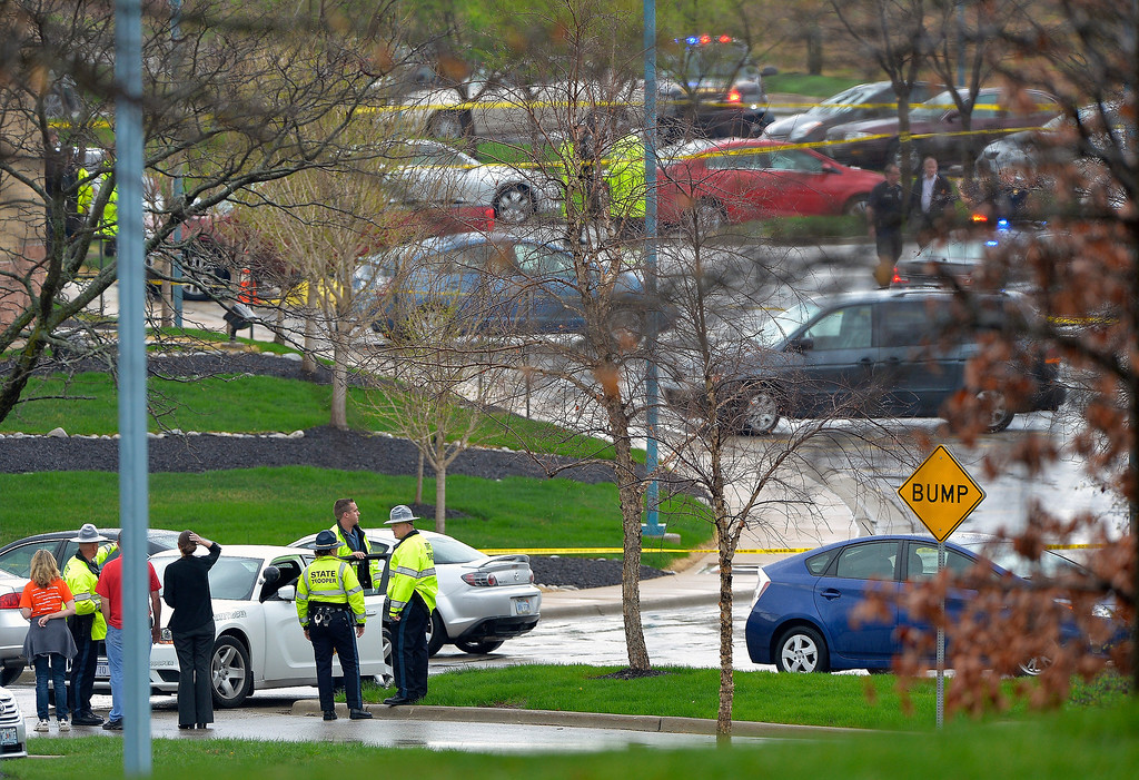 . Kansas State Troopers stand near the location of a shooting at the Jewish Community Center in Overland Park, Kan., Sunday, April 13, 2014.  Overland Park Fire Department spokesman Jason Rhodes said Sunday afternoon that one person of interest is in custody. Rhodes said the shootings happened at two different locations, but did not specify where the shootings happened.  (AP Photo/The Kansas City Star, John Sleezer)