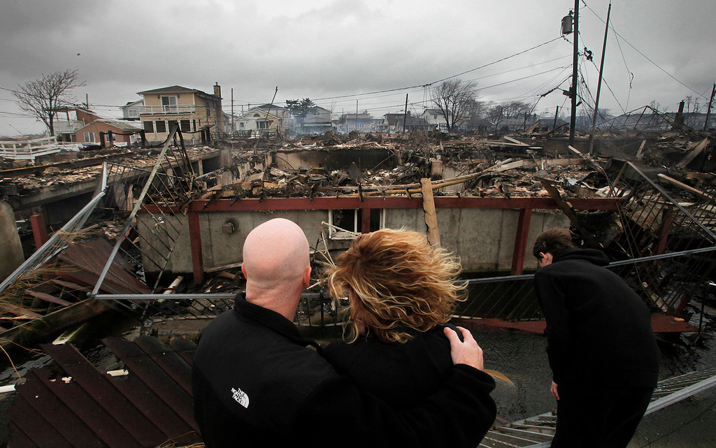 . Robert Connolly, left, embraces his wife Laura as they survey the remains of the home owned by her parents that burned to the ground in the Breezy Point section of New York, Tuesday, Oct. 30, 2012. More than 50 homes were destroyed in the fire which swept through the oceanfront  community during superstorm Sandy. At right is their son, Kyle. (AP Photo/Mark Lennihan)