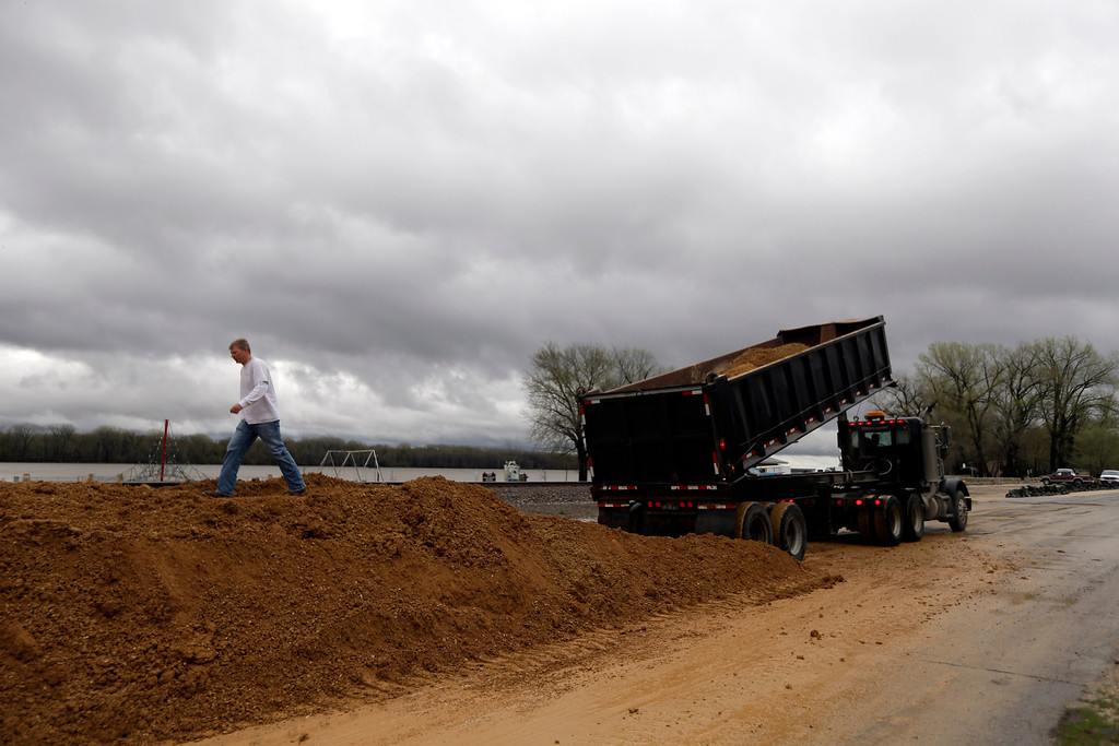 . A man walks along a temporary levee being quickly constructed in hopes of holding back the rising Mississippi River Thursday, April 18, 2013, in Clarksville, Mo.  (AP Photo/Jeff Roberson)