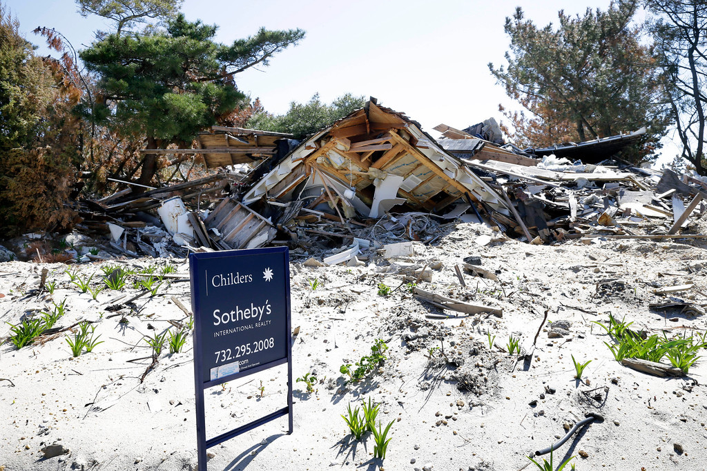 . A realty sign stands Thursday, April 25, 2013, in Mantoloking, N.J., on a lot where the home was destroyed last October by Superstorm Sandy. Six months after Sandy devastated the Jersey shore and New York City and pounded coastal areas of New England, the region is dealing with a slow and frustrating, yet often hopeful, recovery. (AP Photo/Mel Evans)