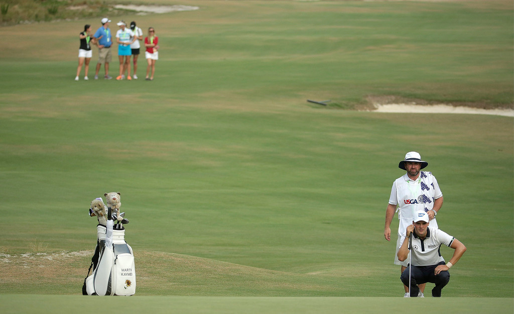 . Martin Kaymer, of Germany, lines up his putt as a group of LPGA players watch from the fairway on the 16th hole during the final round of the U.S. Open golf tournament in Pinehurst, N.C., Sunday, June 15, 2014. The women\'s U.S. Open golf tournament starts Thursday on the same course. (AP Photo/Charlie Riedel)