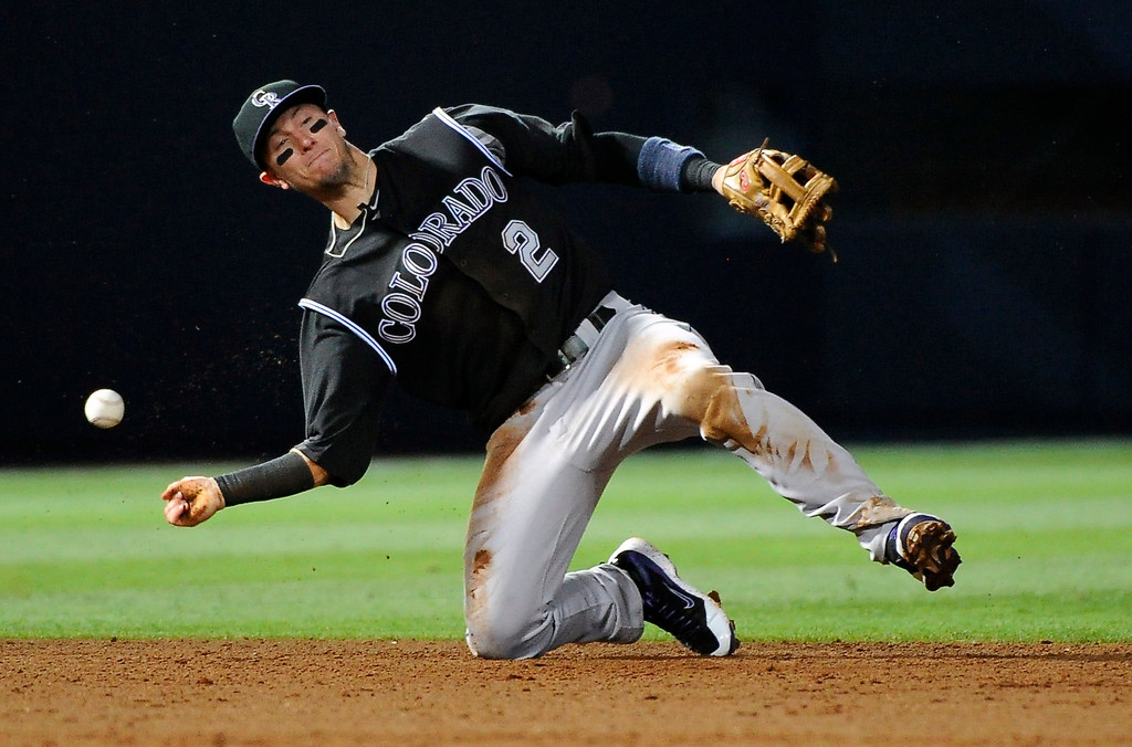 . Colorado Rockies shortstop Troy Tulowitzki loses the ball on an attempted force out of Atlanta Braves\' Tyler Pastornicky during the seventh inning of a baseball game Friday, May 23, 2014, in Atlanta. (AP Photo/David Tulis)