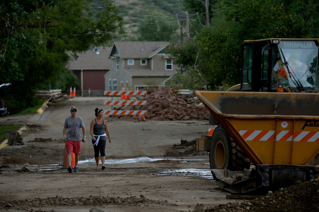 . LYONS, CO. - SEPTEMBER 18: Residents Chris and Kristi Cullen walk down Park Street  near their home in Lyons,  CO September 18, 2013. The couple said, while their home is okay,  it is hard to come back and see the damage.  Business owners were allowed to return to town today and residents will be allowed to visit their homes tomorrow. As emergency personnel methodically make their way from door-to-door of flooded and damaged homes this week, the number of unaccounted-for Coloradans is dropping. The number in Boulder County has fallen to four. (Photo By Craig F. Walker / The Denver Post)