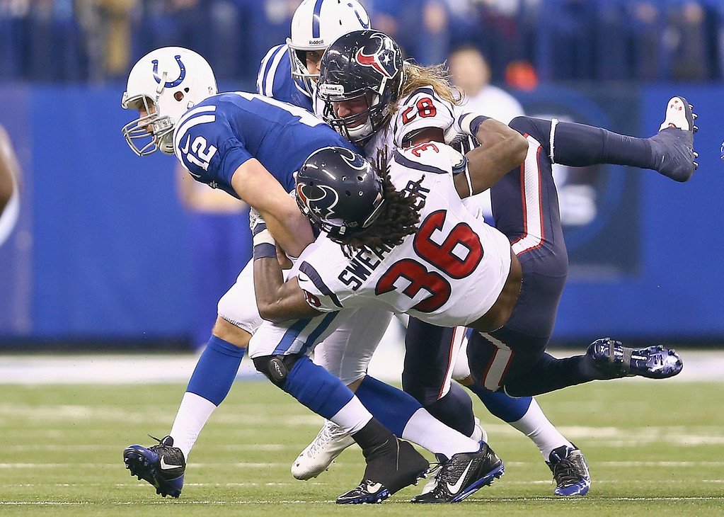 . Andrew Luck #12 of the Indianapolis Colts runs with the ball while tackled by D.J. Swearinger #36 and Brooks Reed #58 of the Houston Texans during the NFL game at Lucas Oil Stadium on December 15, 2013 in Indianapolis, Indiana.  (Photo by Andy Lyons/Getty Images)