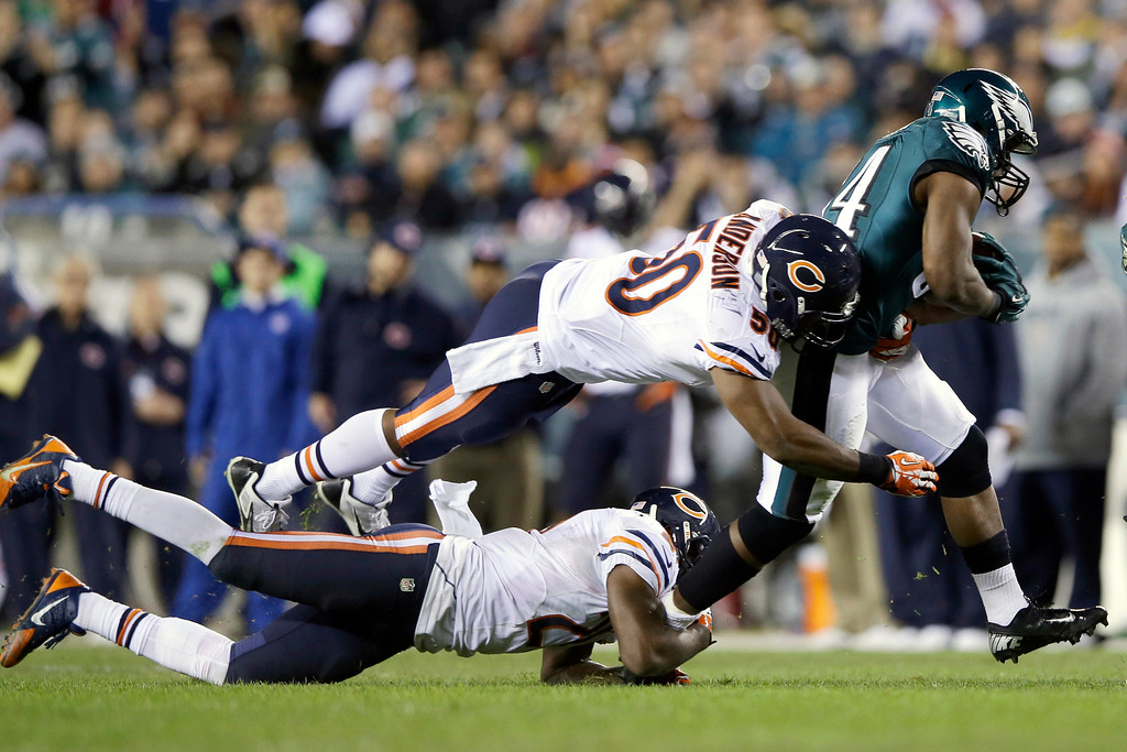 . Philadelphia Eagles\' Bryce Brown, right, breaks free of Chicago Bears\' James Anderson, top left, and Roc Carmichael during the second half of an NFL football game, Sunday, Dec. 22, 2013, in Philadelphia. (AP Photo/Michael Perez)