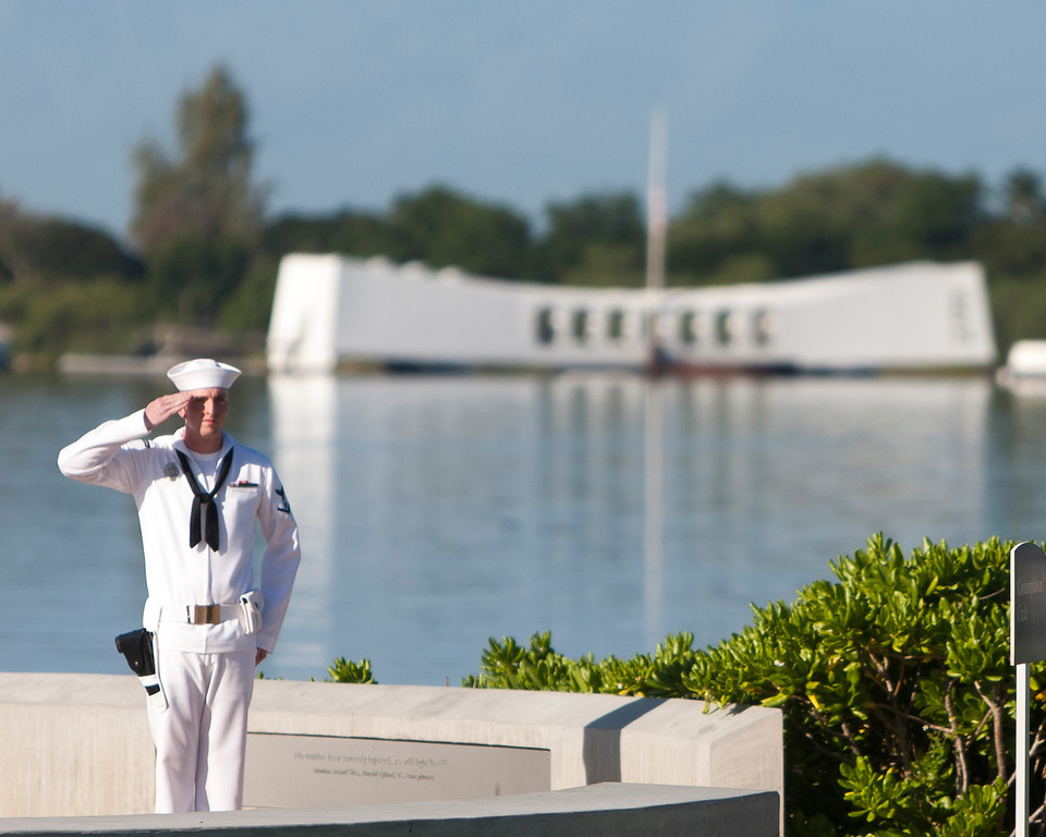 . With the USS Arizona in the background, Navy rifleman stands at attention at the ceremony commemorating the 72nd anniversary of the attack on Pearl Harbor, Saturday, Dec. 7, 2013, in Honolulu.  (AP Photo/Marco Garcia)