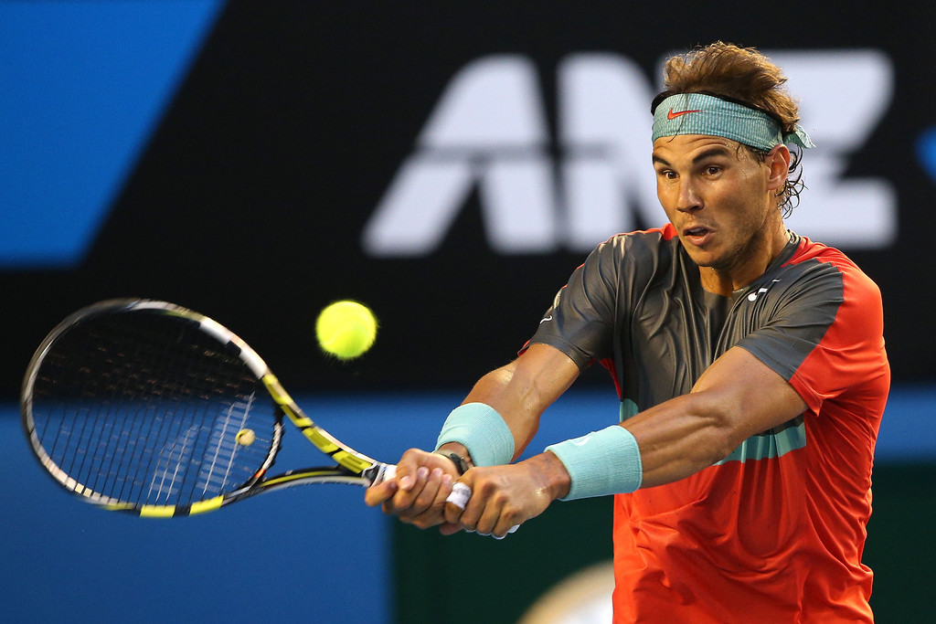 . Rafael Nadal of Spain plays a backhand in his men\'s final match against Stanislas Wawrinka of Switzerland during day 14 of the 2014 Australian Open at Melbourne Park on January 26, 2014 in Melbourne, Australia.  (Photo by Clive Brunskill/Getty Images)