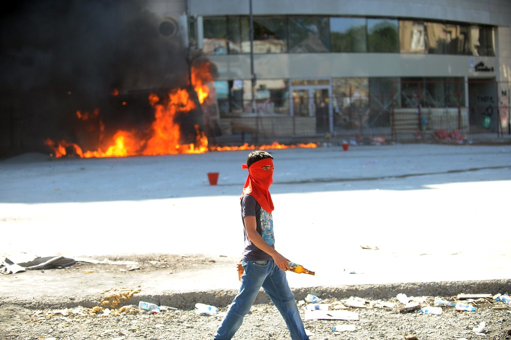 . A protestor walks in front of a burning car on Taksim square on June 11, 2013.  AFP PHOTO / BULENT  KILIC/AFP/Getty Images