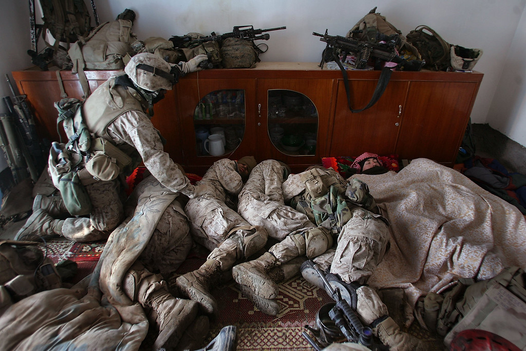 . A U.S. Marine wakes another for his turn on guard duty as the Marines cluster for warmth while sleeping in a house captured by American and Iraqi forces from a man the military says is a former insurgent financier during an operation in Ramadi January 17, 2007 in the Anbar province of Iraq. The combined forces swept into Ramadi under the cover of darkness and began searching neighborhoods for insurgents. Ramadi, with daily combat between insurgents and U.S. led forces, has seen some of the highest casualty rates of the war.  (Photo by John Moore/Getty Images)