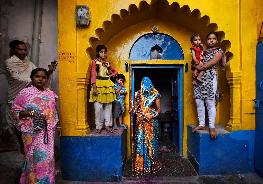 . A newly wed Indian woman from Barsana village waits with a wooden stick at the door step of her house, for the arrival of villagers from Nandgaon during the Lathmar Holy festival the legendary hometown of Radha, consort of Hindu God Krishna, in Barsana, 115 kilometers (71 miles)  from New Delhi, India , Thursday, March 21, 2013. During Lathmar Holi the women of Barsana beat the men from Nandgaon, the hometown of Krishna, with wooden sticks in response to their teasing as they depart the town. (AP Photo/Manish Swarup)