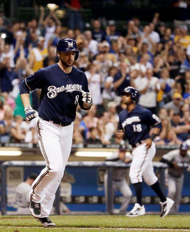 . Milwaukee Brewers\' Ryan Braun heads to first and Khris Davis (18) home after Braun was hit by a pitch with the bases loaded during the seventh inning of a baseball game against the Colorado Rockies on Friday, June 27, 2014, in Milwaukee. (AP Photo/Morry Gash)