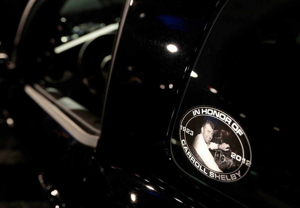 . A picture of racecar driver Carroll Shelby is displayed on a Shelby American Inc., Shelby 1000 at The Gallery in the MGM Grand Detroit ahead of the 2013 North American International Auto Show (NAIAS) in Detroit, Michigan, U.S., on Saturday, Jan. 12, 2013. The Detroit auto show runs through Jan. 27 and will display over 500 vehicles, representing the most innovative designs in the world. Photographer: Jeff Kowalsky/Bloomberg