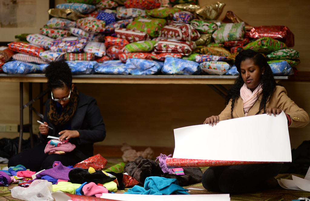 """. DENVER, CO. DECEMBER 21: Mahder Ferede, 19, of Aurora, left, and Sara Dessie, 17, of Denver are  wrapping Christmas gift during the annual Father Woody Christmas Party in Denver, Colorado December 21, 2013. In advance of handing out 5,000 gifts, volunteers are doing a \""""wrapping party\"""" at the Sheraton Denver Downtown Hotel. (Photo by Hyoung Chang/The Denver Post)"""