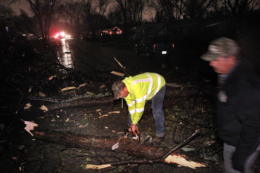 . Workers chainsaw downed tree limbs on Lynn Haven Lane following a strong spring storm in Hazelwood late Wednesday evening, April 10, 2013.  (AP Photo/Erik M. Lunsford, Post-Dispatch)