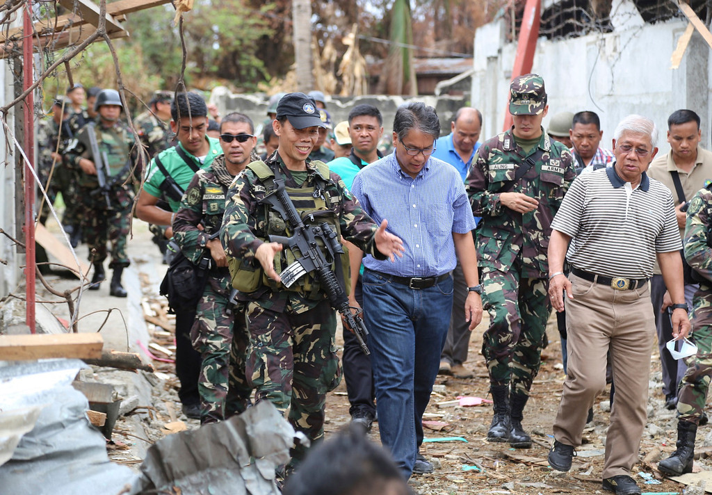 . Interior and Local Government Secretary Mar Roxas, center in blue shirt, and Philippine Secretary of National Defense Voltaire Gazmin, in striped shirt right, tour the site of a three-week intense fighting between Government forces and Muslim rebels who have taken nearly 200 people hostagesin Zamboanga city, southern Philippines, Saturday Sept. 28, 2013. The deadly standoff between government troops and Muslim rebels has ended with all of the captives safe, officials said Saturday. Defense Secretary Voltaire Gazmin said only a handful of Moro National Liberation Front rebels remained in hiding and were being hunted by troops in the coastal outskirts of Zamboanga city, adding authorities were trying to determine if rebel commander Habier Malik, who led the Sept. 9 siege, was dead. More than 200 people were killed in the clashes, including 183 rebels and 23 soldiers and police, in one of the bloodiest and longest-running attacks by a Muslim group in the south, scene of decades-long Muslim rebellion for self-rule in the largely Roman Catholic country. (AP Photo)