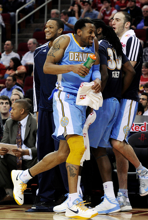 . Denver Nuggets\' Andre Iguodala, center, laughs along the sidelines in the second half of an NBA basketball game against the Houston Rockets Wednesday, Jan. 23, 2013, in Houston. Denver won 105-95. (AP Photo/Pat Sullivan)