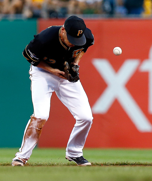 . Clint Barmes #12 of the Pittsburgh Pirates bobbles a ground ball in the sixth inning against the St. Louis Cardinals during Game Three of the National League Division Series at PNC Park on October 6, 2013 in Pittsburgh, Pennsylvania.  (Photo by Jared Wickerham/Getty Images)
