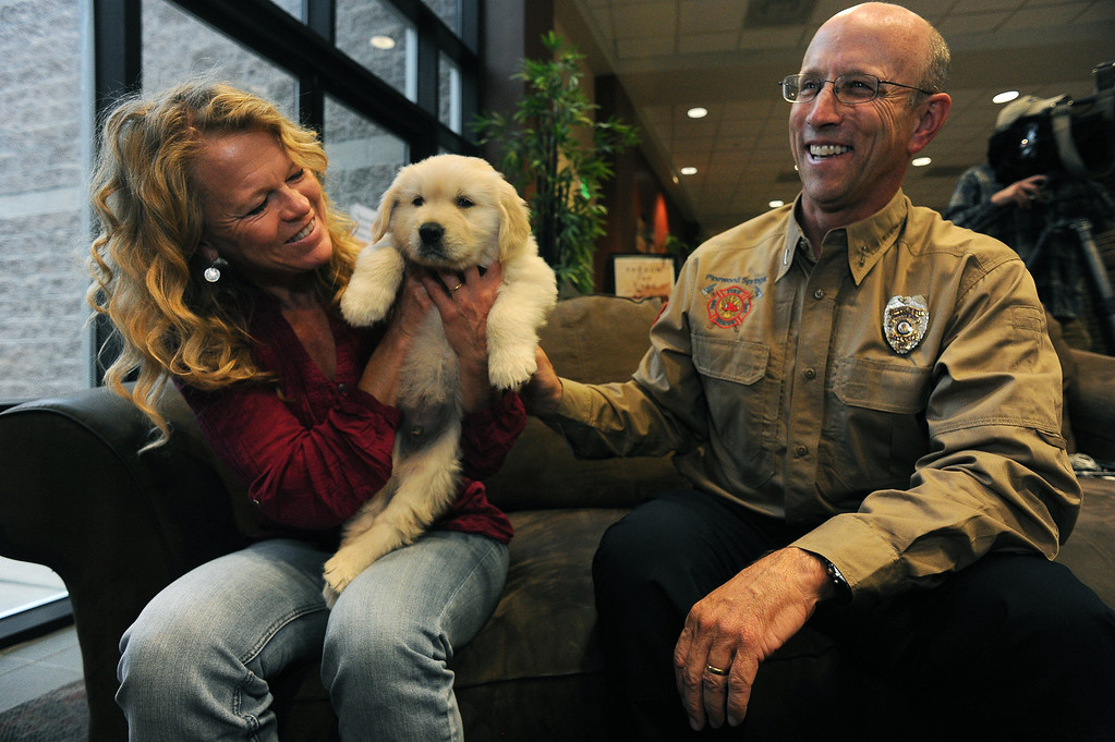 . LONGMONT, CO - OCTOBER 29:   Geri Plank, left, holds 5 week old Chinook as her husband Ted, right, pets the small puppy at Life Bridge Community Church in Longmont, Co on October 29, 2013.   Chinook was born just a few days after the flood.  Her mother was taken out of the Pinewood Springs area via a Chinook helicopter to escape the floods.  Because of this dramatic effort to get the dog to the vet before she gave birth Geri and her husband named this puppy Chinook.  (Photo By Helen H. Richardson/ The Denver Post)
