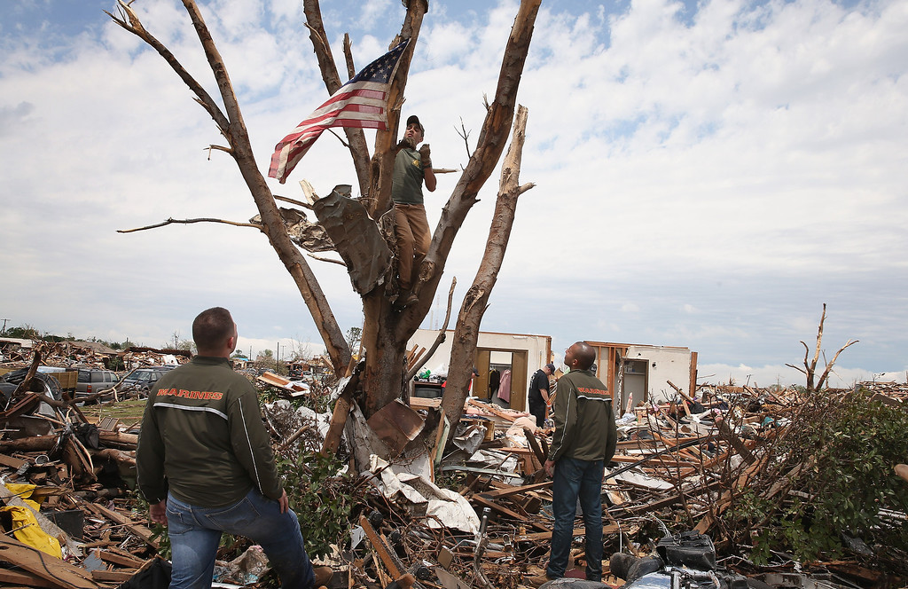 . MOORE, OK - MAY 23:  U.S. Marines Cpl. Dylan Rhodes (L) of Owasso, Oklahoma, Capt. Ray Penny (C) of Houston, TX and Cpl. Patrick Canales of Los Angeles, California recover a flag flying from a tree in front of the destroyed home of Tim Jones and Chritine Jones May 23, 2013 in Moore, Oklahoma. The flag would hang outside the Jones� home on national holidays. On Monday May 20 It was hung in a tree outside of the home after the family returned home to find their house had been leveled by a tornado and the flag tangled in the garage rafters. Today, with the help of the Marines, they decided to preserve the flag. A two-mile wide EF5 tornado touched down in Moore May 20 killing at least 24 people and leaving behind extensive damage to homes and businesses. U.S. President Barack Obama promised federal aid to supplement state and local recovery efforts.  (Photo by Scott Olson/Getty Images)