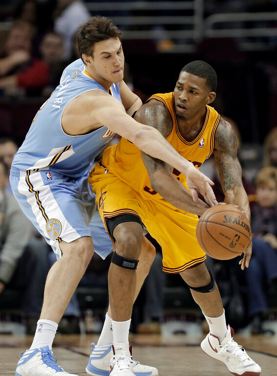 . Denver Nuggets\' Danilo Gallinari, left, from Italy, tries to poke the ball away from Cleveland Cavaliers\' Alonzo Gee during the third quarter of an NBA basketball game Saturday, Feb. 9, 2013, in Cleveland. The Nuggets won 111-103. (AP Photo/Mark Duncan)