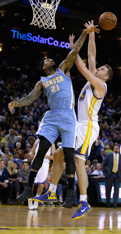 . Wilson Chandler #21 of the Denver Nuggets blocks a shot taken by David Lee #10 of the Golden State Warriors at ORACLE Arena on January 15, 2014 in Oakland, California. (Photo by Ezra Shaw/Getty Images)