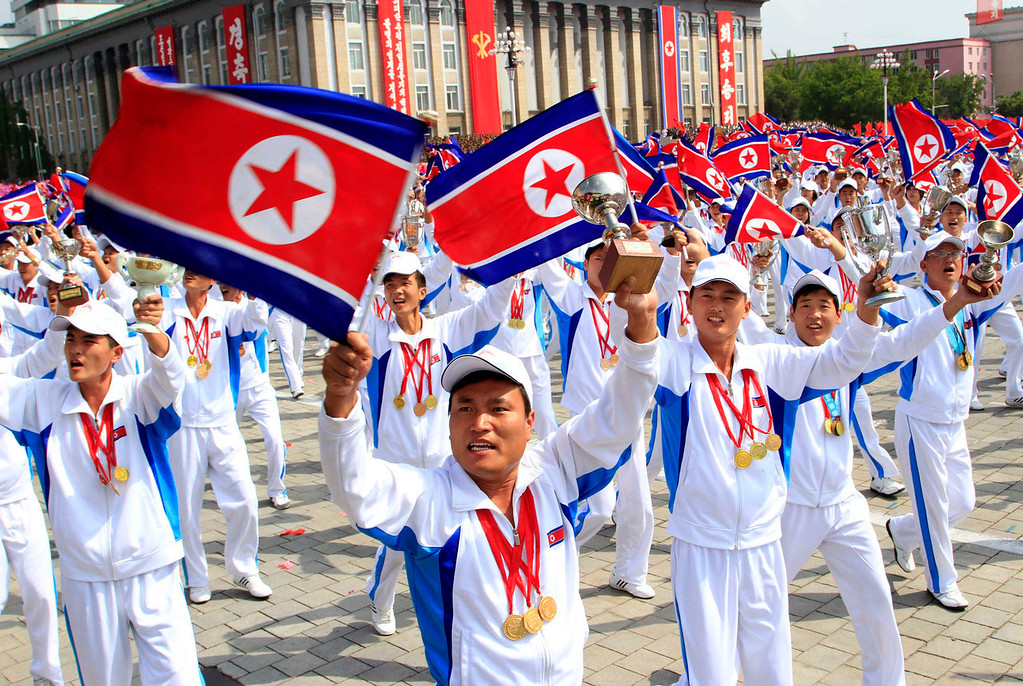 . North Korean athletes wave their national flag and trophies during a military parade at Kim Il Sung Square to mark the 65th anniversary of the country\'s founding in Pyongyang, North Korea, Monday, Sept. 9, 2013. (AP Photo/Jon Chol Jin)