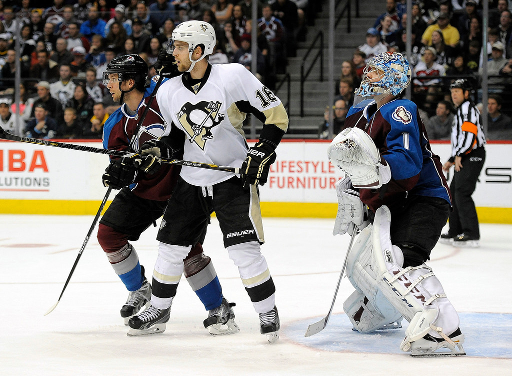 . Colorado Avalanche defenseman Nate Guenin, left, and Pittsburgh Penguins center Brandon Sutter, center, vie for position in front of Colorado Avalanche goalie Semyon Varlamov, right, of Russia, in the third period of an NHL hockey game Sunday, April 6, 2014, in Denver. The Penguins won 3-2 in a shootout. (AP Photo/Chris Schneider)