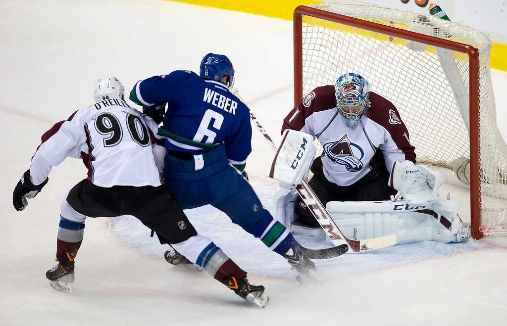 . Colorado Avalanche goalie Semyon Varlamov, right, of Russia, stops Vancouver Canucks\' Yannick Weber, center, of Switzerland, as Colorado\'s Ryan O\'Reilly, left, defends during the second period of an NHL hockey game Thursday, April 10, 2014, in Vancouver, British Columbia. (AP Photo/The Canadian Press, Darryl Dyck)