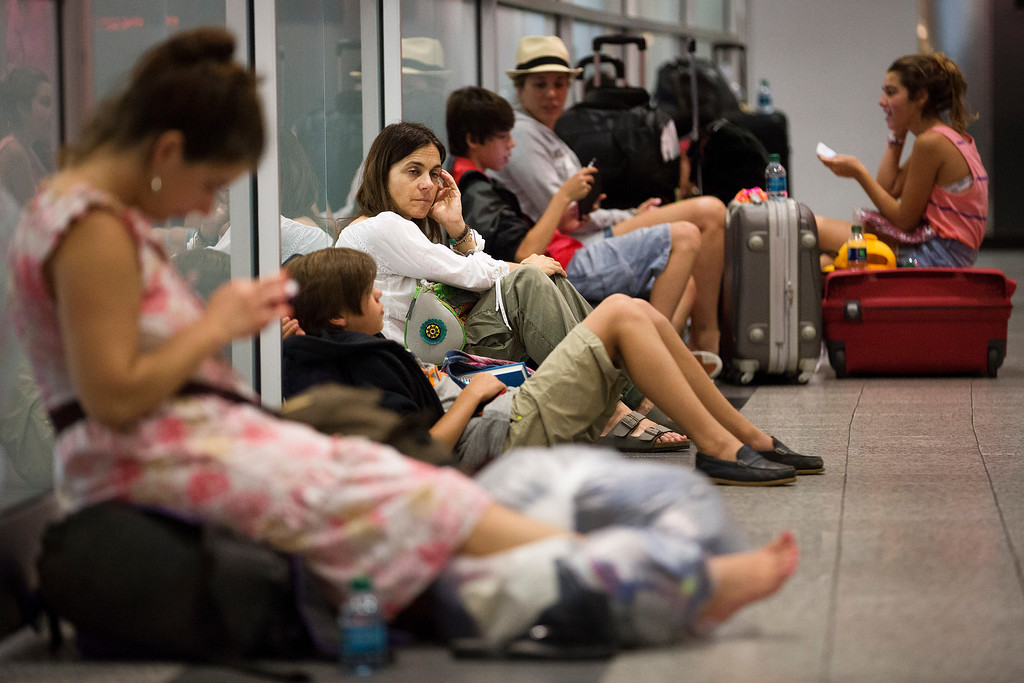 . Stranded passengers wait in LaGuardia Airport as multiple flights were canceled after a Southwest Airlines 737 plane\'s nose gear collapsed during a landing, Monday, July 22, 2013, in New York. The Federal Aviation Administration says the plane landed safely. (AP Photo/John Minchillo)