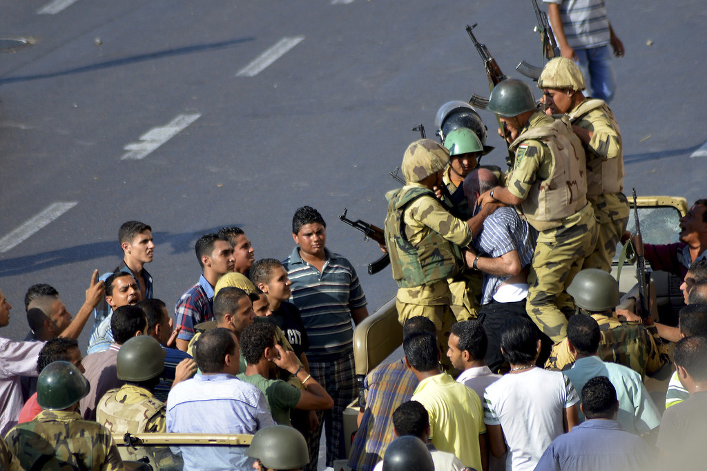 . Egyptian soldiers detain a man during clashes between supporters and opponents of Egypt\'s ousted President Mohammed Morsi in Alexandria, Egypt, Friday, Aug. 30, 2013. Tens of thousands of protesters and Muslim Brotherhood supporters rallied Friday throughout Egypt against a military coup and a bloody security crackdown, though tanks and armored police vehicles barred them from converging in major squares.(AP Photo/Heba Khamis)