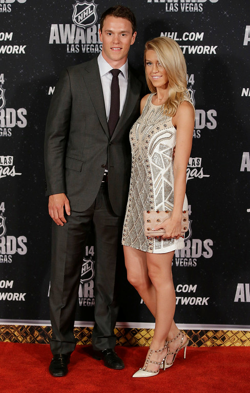 . Jonathan Toews of the Chicago Blackhawks  poses with his girlfriend, Lindsey Vecchione, on the red carpet before the NHL Awards on Tuesday, June 24, 2014, in Las Vegas. (AP Photo/John Locher)