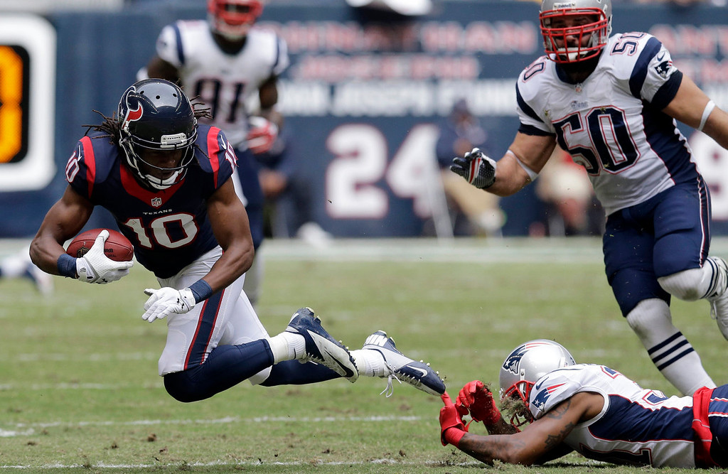 . Houston Texans\' DeAndre Hopkins (10) is tripped by New England Patriots\' Aqib Talib, bottom right, after a reception during the second quarter of an NFL football game on Sunday, Dec. 1, 2013, in Houston. (AP Photo/Patric Schneider)