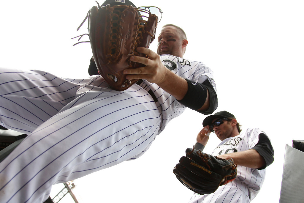 . Colorado Rockies right fielder Michael Cuddyer, left, puts down glove as he returns to dugout with center fielder Charlie Blackmon after helping to retire the Arizona Diamondbacks in the first inning of a baseball game in Denver on Sunday, Sept. 22, 2013. (AP Photo/David Zalubowski)