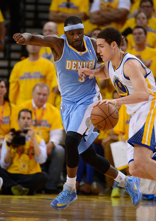 . Ty Lawson (3) of the Denver Nuggets keeps up with Klay Thompson (11) of the Golden State Warriors as tries to drive on him during the second quarter in Game 6 of the first round NBA Playoffs May 2, 2013 at Oracle Arena. (Photo By John Leyba/The Denver Post)