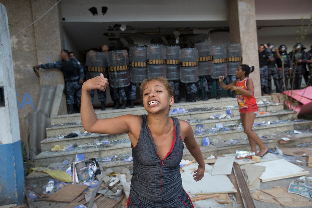 . A woman shouts asking for help during an eviction in Rio de Janeiro, Brazil, Friday, April 11, 2014. Squatters in Rio de Janeiro are clashing with police after a Brazilian court ordered that 5,000 people be evicted from abandoned buildings of a telecommunications company. Officers have used tear gas and stun grenades to try to disperse the families.(AP Photo/Silvia Izquierdo)