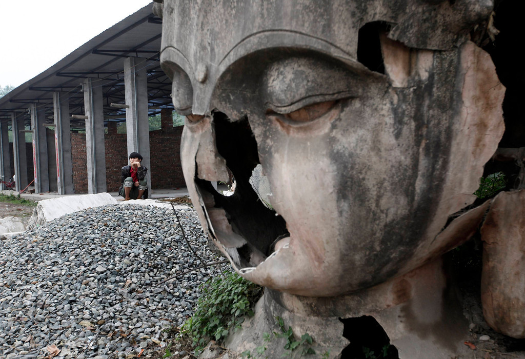 . A survivor smokes near a damaged Buddha statue two days after an earthquake hit Lushan county of Ya\'an, Sichuan province April 22, 2013. REUTERS/Jason Lee
