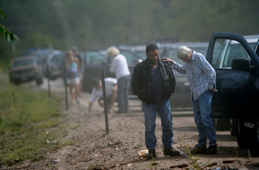 ". LYONS, CO. - SEPTEMBER 19: Lyons resident Jill Babcock, right, talks with Mike Lovato while waiting at a checkpoint at the junction of highways 66 & 36 in Lyons,  CO September 19, 2013. Babcock said she has lived in Lyons since 1978 and and was the police chief for a decade. She said, ""as of Sunday the house was still standing. I got out, my cat got out- that\'s what\'s important.\"" Residents were being allowed to return to their homes Thursday. (Photo By Craig F. Walker / The Denver Post)"