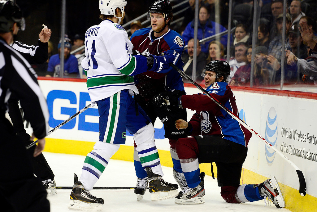 . DENVER, CO - MARCH 24: Jamie McGinn (11) of the Colorado Avalanche shoves Andrew Alberts (41) of the Vancouver Canucks after he checked P.A. Parenteau (15) to the ice during the third period of action. The Colorado Avalanche lost to the Vancouver Canucks 3-2 at the Pepsi Center. (Photo by AAron Ontiveroz/The Denver Post)