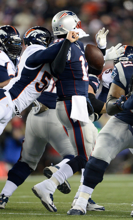 . Denver Broncos outside linebacker Von Miller (58) hits New England Patriots quarterback Tom Brady (12) from behind to force a fumble during the first quarter November 24, 2013 at Gillette Stadium. The ball was picked up by Denver Broncos defensive tackle Terrance Knighton.  (Photo by John Leyba/The Denver Post)