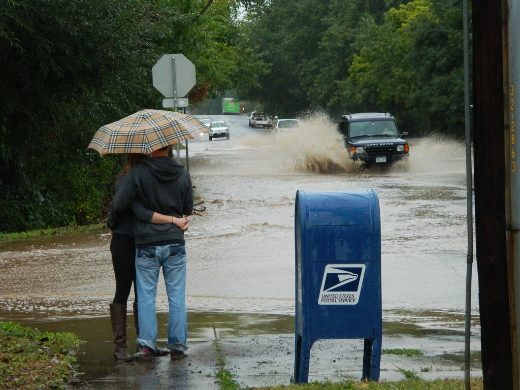 . Couple watches cars drive thru a river on their street. Photo by Jae Beaubier