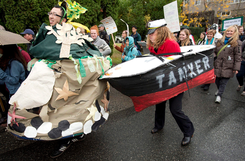 . A demonstrator dressed up as a tanker bangs into a demonstrator dressed up as an island during a anti-pipeline protest march to Premier Christy Clark\'s office in Vancouver, on Oct. 24, 2012.   (AP Photo/The Canadian Press, Jonathan Hayward)