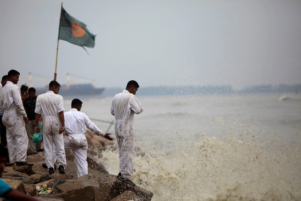 . Bangladeshi marine sailors stand on the banks of the Bay of Bengal sea, as they prepare for the coming of tropical cyclone Mahasen, in Chittagong, Bangladesh, Wednesday, May 15, 2013. People living in coastal areas in Bangladesh and Myanmar are being evacuated as cyclone Mahasen appears to make landfall late Thursday or early Friday, according to news reports. (AP Photo/A.M. Ahad)