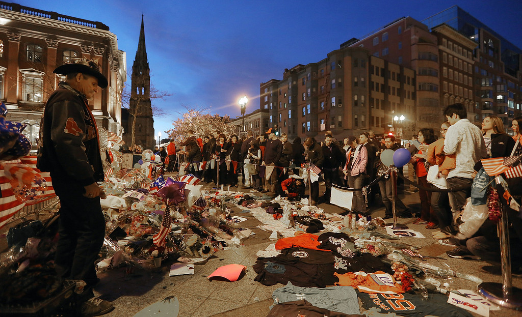 . BOSTON, MA - APRIL 20:  People gather at a makeshift memorial for victims near the site of the Boston Marathon bombings a day after the second suspect was captured on April 20, 2013 in Boston, Massachusetts.  A manhunt for Dzhokhar A. Tsarnaev, 19, a suspect in the Boston Marathon bombing ended after he was apprehended on a boat parked on a residential property in Watertown, Massachusetts. His brother Tamerlan Tsarnaev, 26, the other suspect, was shot and killed after a car chase and shootout with police. The bombing, on April 15 at the finish line of the marathon, killed three people and wounded at least 170.  (Photo by Mario Tama/Getty Images)
