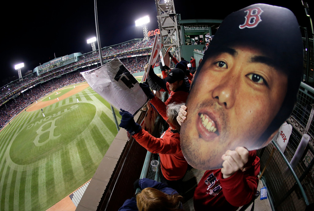 . Fans hold a large photo of Red Sox relief pitcher Koji Uehara and cheer during the ninth inning of Game 2 of baseball\'s World Series between the Red Sox and the St. Louis Cardinals Thursday, Oct. 24, 2013, in Boston. (AP Photo/Charlie Riedel)