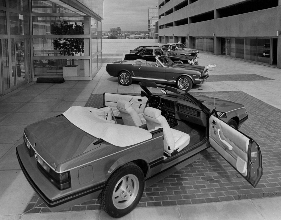 . New Mustang convertible, foreground, is more compact than its 1965 ancestor, shown together in Galleria area of Denver Center for the Performing Arts, 1982. Credit: The Denver Post