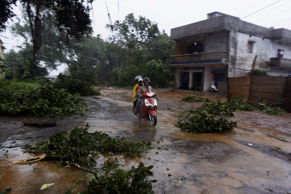 . Motorcyclist  drives past fallen trees during heavy rain and winds near Gopalpur beach in Ganjam district about 200 kilometers  (125 miles) from the eastern Indian city Bhubaneswar, India, Saturday, Oct. 12, 2013. Hundreds of thousands of people living along India\'s eastern coastline were taking shelter Saturday from a massive, powerful cyclone Phailin that was set to reach land packing destructive winds and heavy rains. (AP Photo/Biswaranjan Rout)