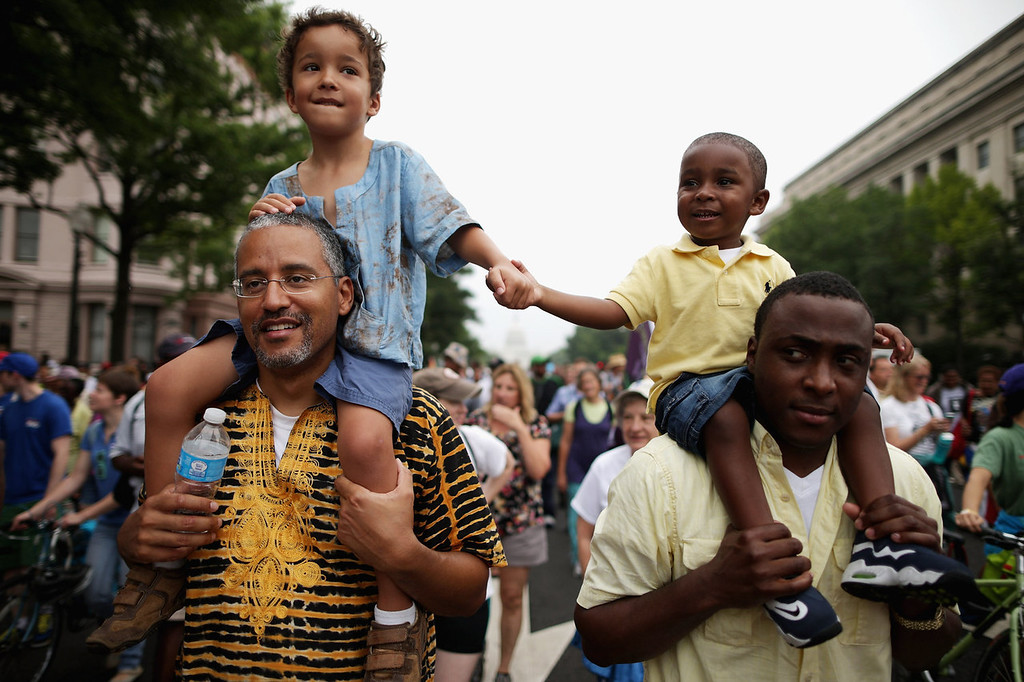 ". (L-R) John Mbugua and his son Giovanni Mbugua, 6, of San Jose, California, and Lavon Johnson and his son Mason Johnson, 2, of Fort Meade Maryland, hold hands while marching with thousands of other people from Capitol Hill to the Lincoln Memorial during the \'Let Freedom Ring Commemoration and Call to Action\' honoring the 50th anniversary of the historic March on Washington for Jobs and Freedom August 28, 2013 in Washington, DC. The 1963 landmark civil rights event was where Dr. Martin Luther King Jr. delivered his famous speech, saying, \'I still have a dream, a dream deeply rooted in the American dream...one day this nation will rise up and live up to its creed, ""We hold these truths to be self evident: that all men are created equal.\"" I have a dream . . .\'  (Photo by Chip Somodevilla/Getty Images)"