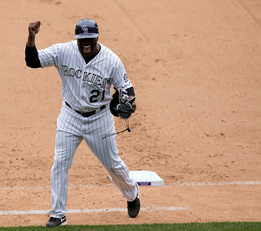 . First base coach Eric Young of the Colorado Rockies celebrates a walk-off two-run home run by Justin Morneau #33 in the 10th inning against the San Diego Padres at Coors Field on May 18, 2014 in Denver, Colorado. The Rockies defeated the Padres 8-6 in 10 innings. (Photo by Justin Edmonds/Getty Images)