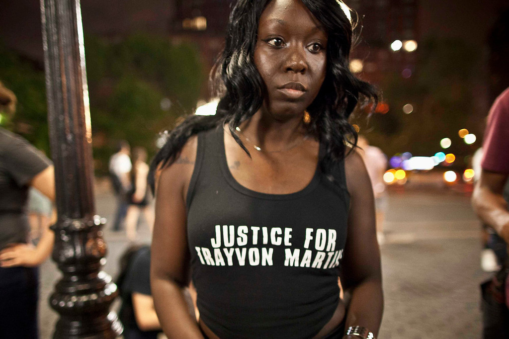 ". Brooklyn Nimoh of New York wears a ""Justice For Trayvon Martin\"" shirt as people gather at Union Square in response to the acquittal of George Zimmerman in the Trayvon Martin trial, in New York July 14, 2013. A Florida jury acquitted George Zimmerman on Saturday in the shooting death of unarmed black teenager Trayvon Martin in a case that sparked a national debate over racial profiling and self-defense laws. REUTERS/Andrew Kelly"